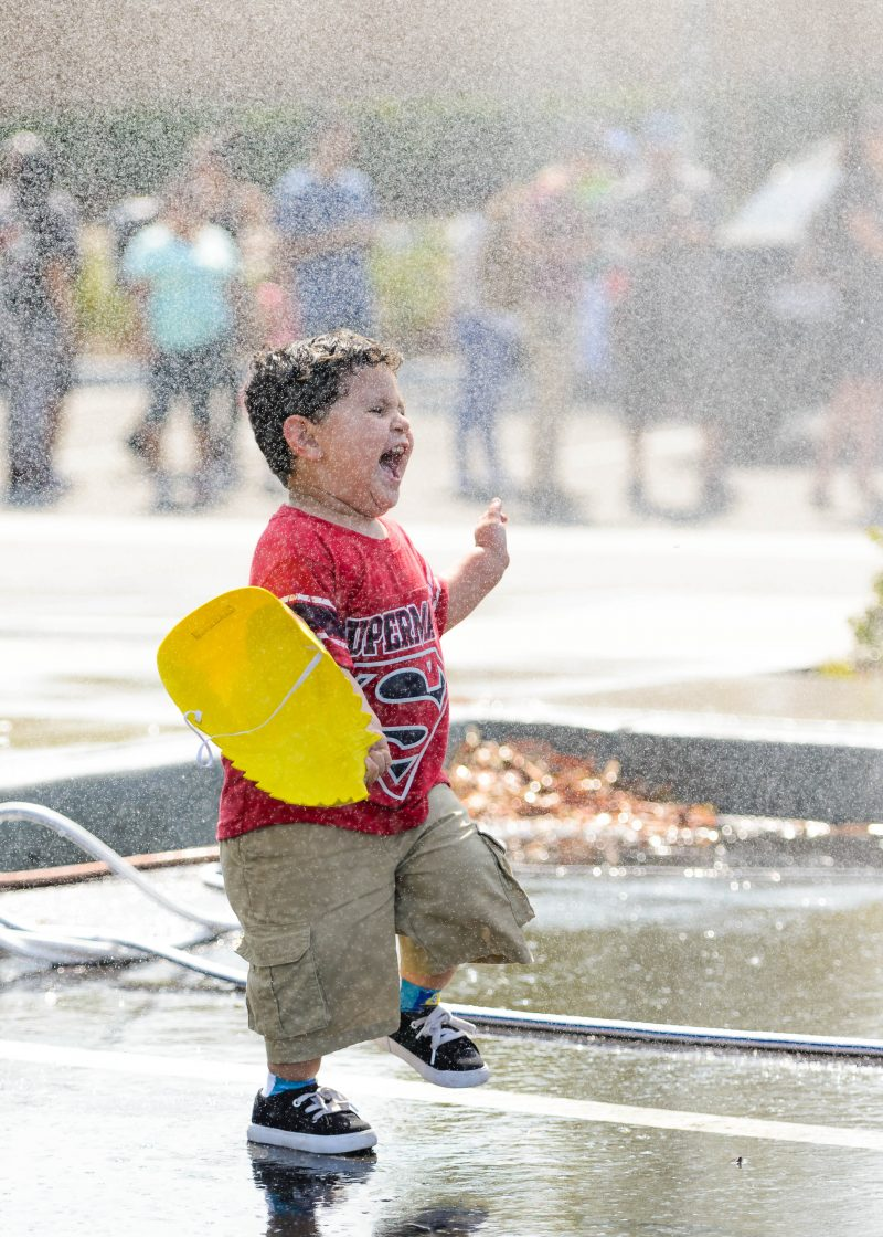 Kid enjoys worry-free happiness playing with water sprinkles at a charity event